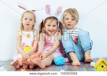 Three smiling preschoolers with Easter bunny ears on