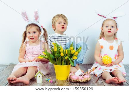Attractive preschool boy and two girls celebrating Easter