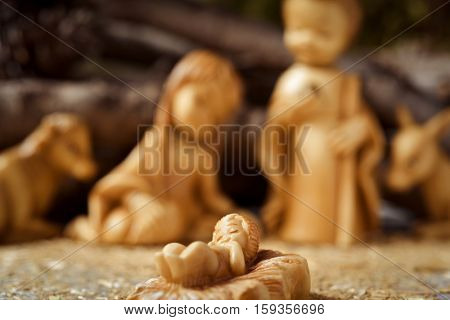 the holy family, the Child Jesus, the Virgin Mary and Saint Joseph, and the donkey and the ox in a rustic nativity scene, with the focus on the Child Jesus