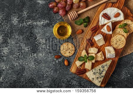 Assortment of cheese with honey nuts and grape on a cutting board top view.