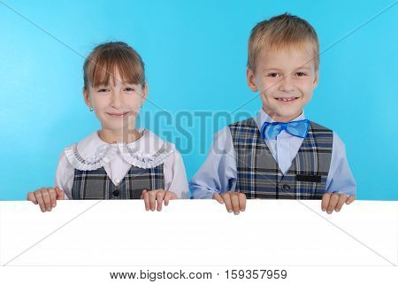 Boy and girl smiling and holding a white banner isolated on blue background