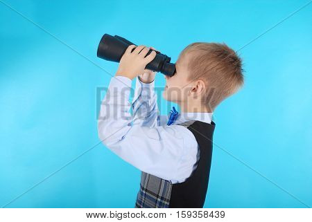 Curious schoolboy looking through binoculars. Photos on a blue background