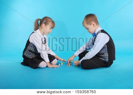 Schoolboy and schoolgirl playing with candy. Photos on a blue background