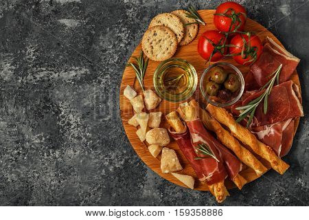 Cheese and meat appetizer selection. Prosciutto parmesan bread sticks olives tomatoes on wooden board top view.