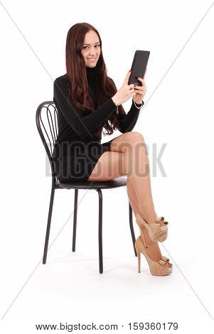 Girl sits on a chair and holding a tablet computer isolated on white