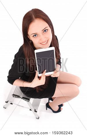 Happy student teenage girl sitting on the ladder and showing a tablet display application isolated on white.