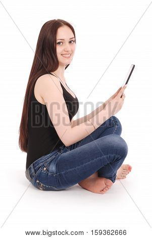 Happy student teenage girl sitting sideways on the floor with tablet pc isolated on white