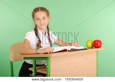Girl in a school uniform sitting at a desk and reading a book isolated on green