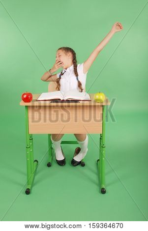 Girl in a school uniform sitting at a desk and yawns isolated on green