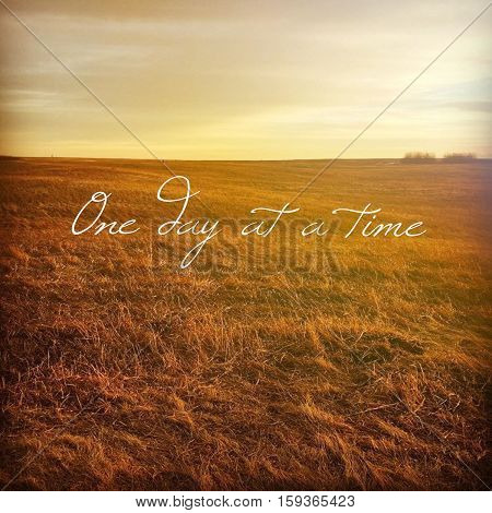 Inspirational quote on scenic field landscape with bright sky, orange grass and isolated bushes at sunset.  Peaceful prairie sunset field landscape view. Bright sky. Lighting effects.
