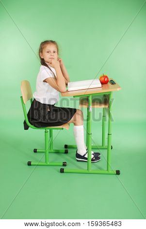 Education people children and school concept - young school girl sitting at table with book over green