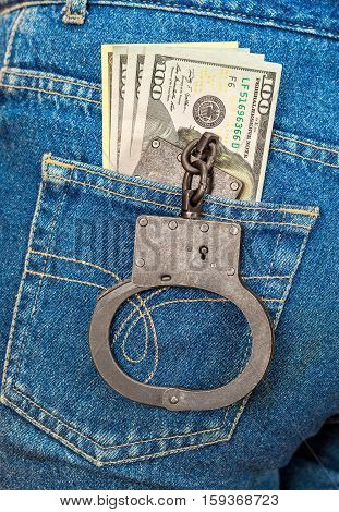Black metal handcuffs and american currency in back jeans pocket