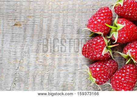 Ripe raspberry close up on wooden background