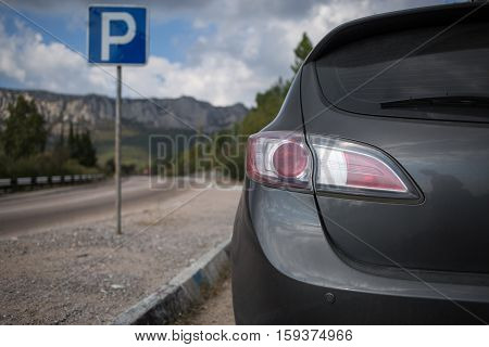 Car and blue parking sign with blurred road and mountains at the background