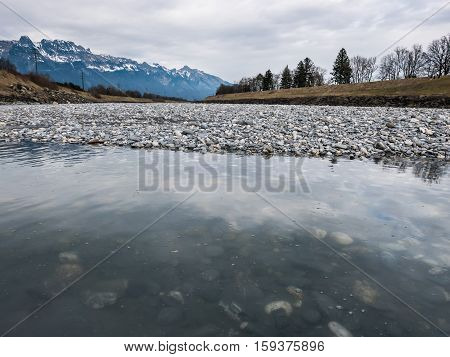 Rocks Next To The River Rhein With The Mountains In The Background