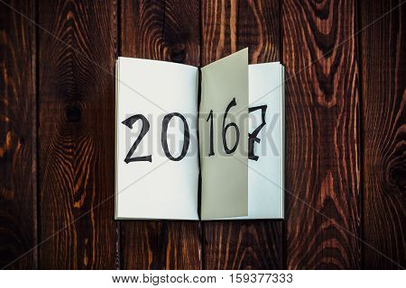 New year concept for 2017 - opened notepad on wooden rustic background, written 2016, 2017 can be seen on the next page. Copy space. Top view