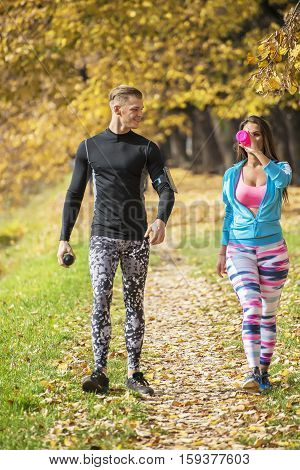 Beautiful Young Couple Cooling Down After Running In The Park. Autumn Environment.