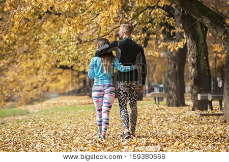 Beautiful Young Couple Walking Together In The Park. Back View. Autumn Environment.