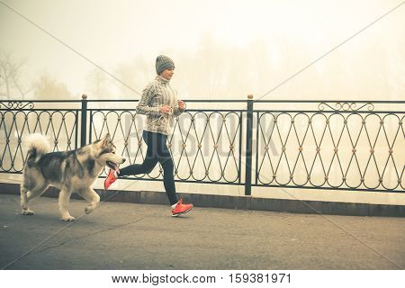 poster of Image of young girl running with her dog, alaskan malamute, outdoor at autumn or winter. Mourning jogging. Domestic pet. Husky. Guide-dog