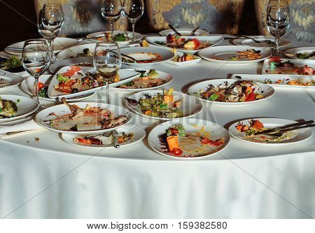 Leftovers or residues of food after banquet dinner restaurant meal on dirty and empty plates or dishes with forks knives and wine glasses on white tablecloth on round table