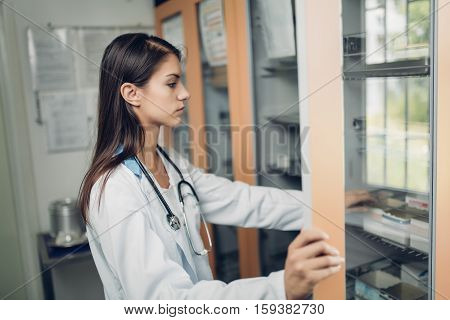 Health care concept.Portrait of a doctor in a dispensary taking medicines from show-case.Medical accessories.Emergency room.Seasonal influenza vaccine.