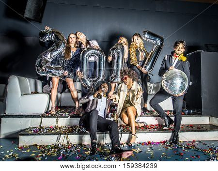 Multi-ethnic group of friends celebrating the end of the year in a nightclub - Sylvester party clubbers having party on new year's eve