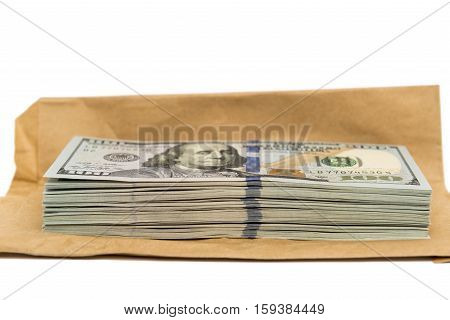 Isolated stack of hundred dollar bills on top of brown envelope