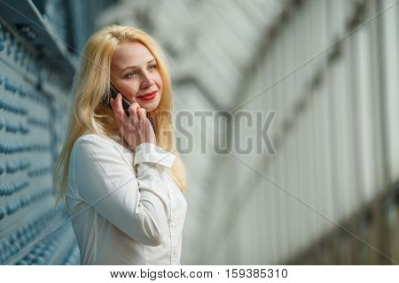 Portrait indoor of beautiful young businesswoman with long blond hair talking on mobile phone and smiling