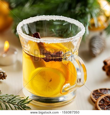 Glass of traditional hot drink on table by Christmas tree with decorations. Citrus tea.