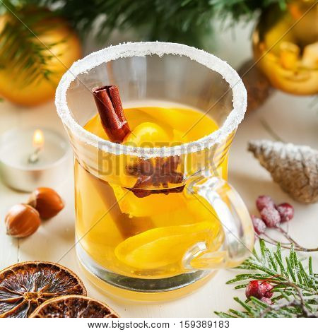 Mulled cider with fruits and spices for Christmas Eve party by tree with decorations. Top view.