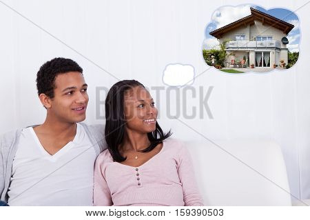 Young Happy Couple Sitting On Sofa Dreaming Of Getting Their Own House