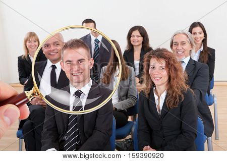 Person Holding Magnifying Glass On The Successful Businessperson For The Recruitment In Job