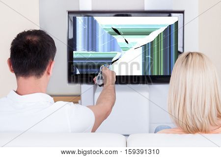 Couple With Remote Control In Front Of Television Showing Distorted Screen At Home