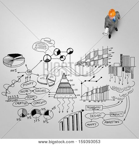 Top view of businessman with megaphone and plan sketches on floor