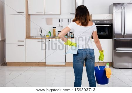 Rear View Of Woman Holding Cleaning Tools And Products In Bucket At Kitchen