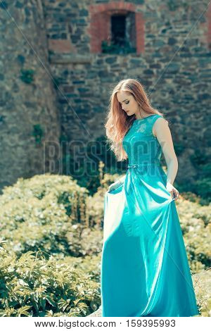 pretty young sexy woman or girl with cute face and long hair in fashionable blue dress sunny outdoor with green leaves on stony wall background