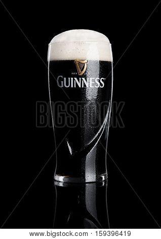 LONDON UK - NOVEMBER 29 2016: Glass of Guinness original beer on black background. Guinness beer has been produced since 1759 in Dublin Ireland.