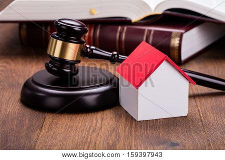 Close-up Of House Model With Gavel On Wooden Table In Courtroom