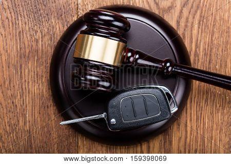 Car Key On Judges Gavel At Wooden Desk In Courtroom