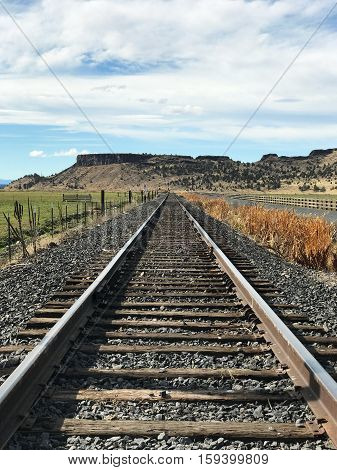Railroad tracks run along farmland in Crook County in Central Oregon on a fall afternoon.
