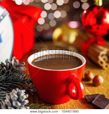 Cup of hot cocoa beverage under Christmas tree gift boxes on background. Traditional hot chocolate beverage.