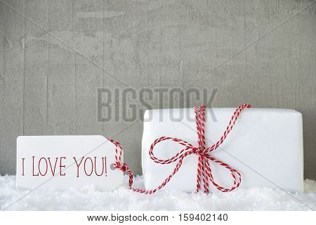 One Christmas Gift Or Present On Snow With Red Ribbon. Cement Or Concrete Wall As Background. Modern And Urban Style. Card For Birthday Or Seasons Greetings. Label With English Text I Love You