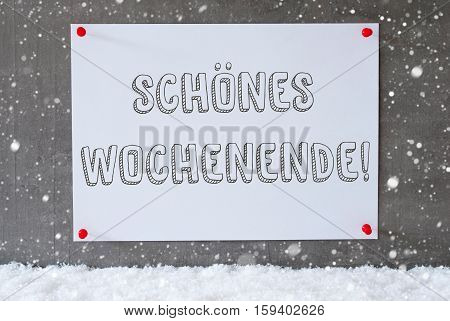 Label With German Text Schoenes Wochenende Means Happy Weekend. Urban And Modern Cement Wall As Background On Snow With Snowflakes.