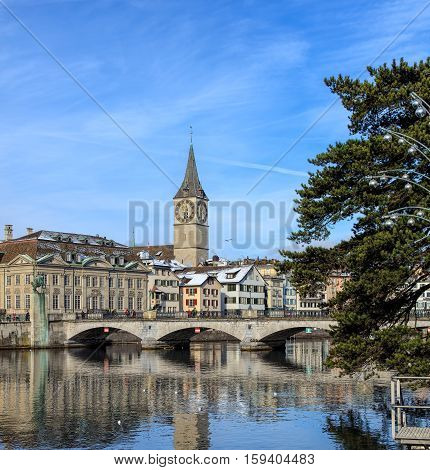 Zurich, Switzerland - 18 January, 2016: the Muensterbruecke bridge over the Limmat river, clock tower of the St. Peter church and old town buildings in the background. Zurich is the largest city in Switzerland.
