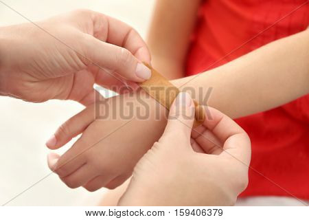 Woman applying sticking plaster to little girl's wrist, close up view