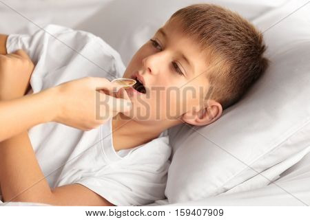 Small sick boy taking medicine in bed