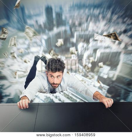 Businessman holding onto the edge of a skyscraper to avoid falling