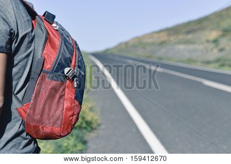 closeup of a young caucasian man seen from behind carrying a backpack standing next to a minor road