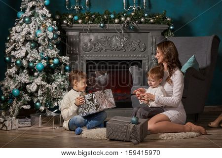 Happy family with  gift boxes are sitting near Christmas tree at home. Merry Christmas and Happy New Year. Beautiful young mother with two sons.