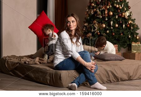 Happy family are playing on a bed near Christmas tree at home. Merry Christmas and Happy New Year. Beautiful young mother with two sons.